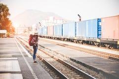 Женщины путешественника и туриста нося рюкзак держа карту, ждать поезд Стоковое Изображение RF