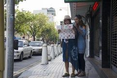 2 женщины путешественника тайских читая путеводитель для путешествия Джорджтауна Стоковые Изображения RF