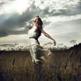 женщины пшеницы скачки поля Стоковые Изображения