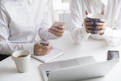 2 женщины работая в офисе с кофе и тетрадью Стоковые Изображения RF