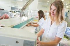 Женщины работая в промышленной прачечной Стоковое Фото