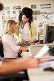 2 женщины работая на столах в многодельном творческом офисе Стоковые Изображения