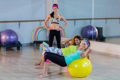 Женщины работая на шарике тренировки с женским тренером Стоковое Изображение