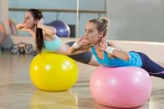 2 женщины работая на шарике тренировки Стоковые Изображения