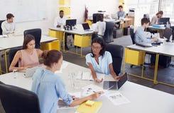 3 женщины работая совместно в занятом офисе, повышенном взгляде Стоковые Фотографии RF