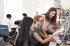 3 женщины работая совместно на компьютере в открытом офисе плана Стоковые Изображения
