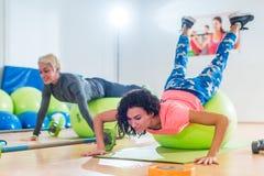 2 женщины работая с делать шариков стабильности нажим-поднимают в классе спортзала Стоковое фото RF