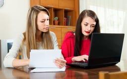 Женщины работая с тетрадью и документами Стоковое Изображение RF