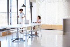 2 женщины работая с цифровой таблеткой в пустом конференц-зале Стоковая Фотография