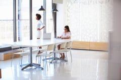 2 женщины работая с цифровой таблеткой в пустом конференц-зале Стоковое Изображение RF