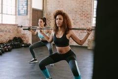 Женщины разрабатывая в спортзале с штангой Стоковые Изображения