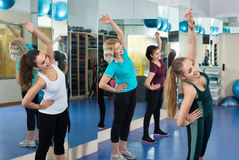 Женщины разрабатывая на аэробном классе в современном спортзале Стоковое Изображение