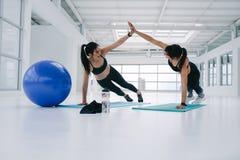Женщины разрабатывая совместно на студии фитнеса Стоковая Фотография RF