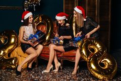 Женщины раскрывая подарки на рождестве торжества Стоковые Фотографии RF
