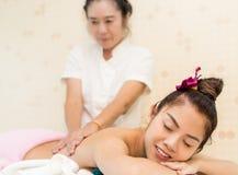 Женщины расслабляющие на кровати курорта пока терапевт масло массажируя ее назад Стоковое Изображение RF