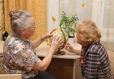 2 женщины рассматривают глобус Стоковая Фотография