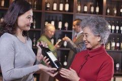 2 женщины рассматривая вино на магазине вина Стоковое фото RF