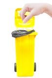 Женщины руки выбирают задвижку, желтые мусорные ведра изолированные на белизне Стоковая Фотография RF