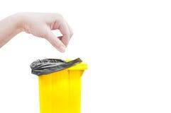 Женщины руки выбирают задвижку, желтые мусорные ведра изолированные на белизне Стоковые Изображения RF