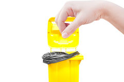 Женщины руки выбирают задвижку, желтые мусорные ведра изолированные на белизне Стоковые Фотографии RF