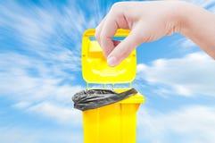 Женщины руки выбирают задвижку, желтые мусорные ведра на голубом небе Стоковые Изображения RF