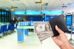 Женщины руки держат деньги в черном бумажнике на банке Стоковое Изображение