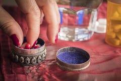 Женщины руки принимают капсулы красные и белые в коробочке для таблеток Стоковые Изображения