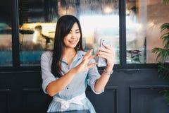 Женщины сидя в мобильном телефоне пользы кафа для сообщения Стоковая Фотография