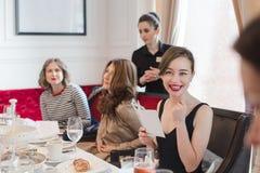 Женщины сидя на, который служат таблице Стоковое Изображение