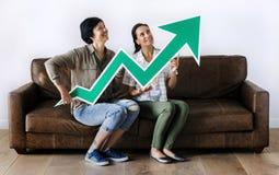 Женщины сидя на кресле и держа значок статистик Стоковые Изображения RF