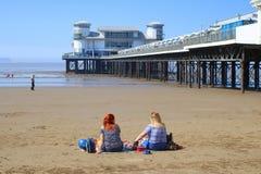 2 женщины сидя на пляже около пристани удовольствия Стоковое Изображение RF