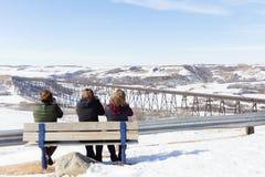 3 женщины сидя на скамейке в парке в зимнем времени Стоковые Фото
