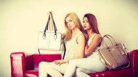 2 женщины сидя на софе представляя сумки Стоковое Фото
