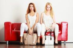 2 женщины сидя на софе представляя сумки Стоковое фото RF
