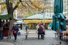 Женщины сидя на таблице внешнего кафа на известном Viktualienmarkt Стоковое Изображение