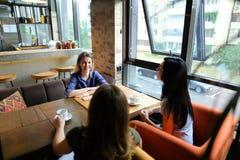 Женщины сидя на уютном кофе кафа, усмехаться и выпивать Стоковое Изображение RF