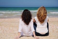 2 женщины сидят на пляже Стоковые Изображения RF