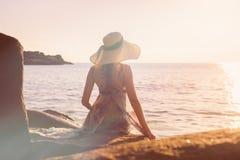 Женщины сидят на утесе на пляже Стоковые Фотографии RF