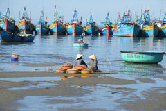 2 женщины сидят с их задвижкой между рыбацкими лодками Гавань рыб в Ne Mui, Вьетнаме Стоковое Фото