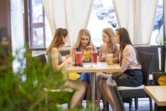 Женщины сидя вокруг таблицы есть десерт Стоковое Изображение RF