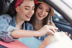 Женщины сидя в автомобиле с их приобретениями Стоковая Фотография