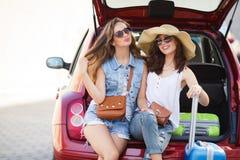 2 женщины сидя в открытом багажнике автомобиля Стоковые Фото
