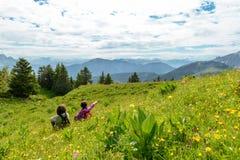 2 женщины сидя в траве и смотря ландшафт Стоковые Фото