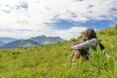 2 женщины сидя в траве и смотря ландшафт Стоковое фото RF