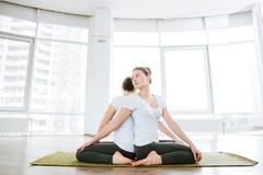 2 женщины сидя и практикуя йога в студии совместно Стоковые Изображения RF