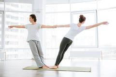 2 женщины сидя и протягивая в центре йоги Стоковое Изображение RF