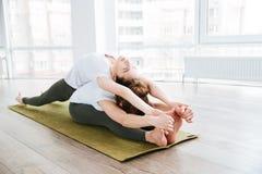 2 женщины сидя и протягивая в центре йоги Стоковые Фото