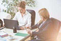 Женщины сидя и работая в офисе Стоковое Изображение RF
