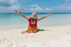Женщины сидя и свобода руки на пляже Стоковые Фотографии RF