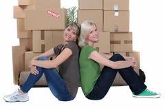 Женщины сидя коробками стоковые фото